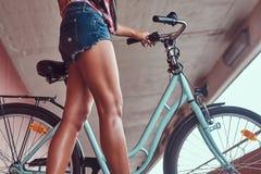 Изображение конца-вверх ровных тонких женских ног в голубых тапках около велосипеда города Стоковые Фотографии RF