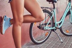 Изображение конца-вверх ровных тонких женских ног в голубых тапках, полагаясь против розовой стены, около голубого велосипеда гор Стоковое Изображение