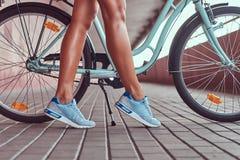 Изображение конца-вверх ровных тонких женских ног в голубых тапках около велосипеда города Стоковые Изображения