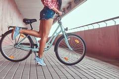 Изображение конца-вверх ровных тонких женских ног в голубых тапках около велосипеда города Стоковые Изображения RF