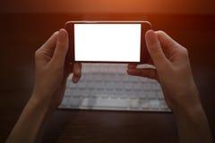 Изображение конца-вверх рук женщины используя смартфон с пустым модель-макетом на предпосылке клавиатуры стоковая фотография
