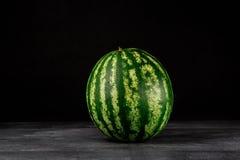 Изображение конца-вверх свежего и совершенного круглого striped арбуза на черной предпосылке Целительный и натуральные продукты с Стоковое Фото