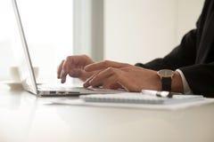 Изображение конца поднимающее вверх укомплектовывает личным составом руки в наручных часах печатая на компьтер-книжке Стоковые Фото