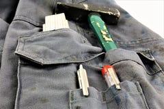 Изображение концепции работая брюки с инструментами в его карманн стоковые фото
