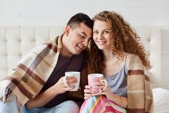 Изображение кофе или чая молодых счастливых пар выпивая в кровати в ут стоковое фото
