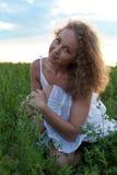 Изображение красивейшей женщины сидя на траве Стоковые Фото
