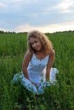 Изображение красивейшей женщины сидя на траве Стоковое Фото