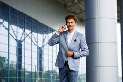 Изображение красивого молодого redhaired бизнесмена говоря на телефоне Стоковое фото RF