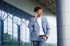 Изображение красивого молодого redhaired бизнесмена говоря на телефоне смотря в сторону Стоковая Фотография