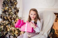 Изображение красивой девушки при подарочные коробки сидя на кресле дома рождество предпосылки украсило вал Стоковые Изображения