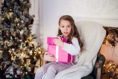 Изображение красивой девушки при подарочные коробки сидя на кресле дома рождество предпосылки украсило вал Стоковые Фото