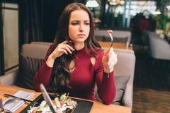 Изображение красивой женщины сидя на таблице в ресторане и есть ее салат Она приняла часть встречи на Стоковое Изображение