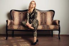 Изображение красивой роскошной женщины сидя на кресле года сбора винограда золота Стоковое Фото