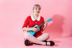 Изображение красивой dollish девушки при короткие светло-фиолетовые волосы нося красное платье играя голубую гавайскую гитару над Стоковые Изображения RF