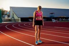 Изображение красивых молодых европейских женских бегуна или спринтера стоя на внешнем следе стадиона, чувствуя вымотанный позже Стоковая Фотография RF