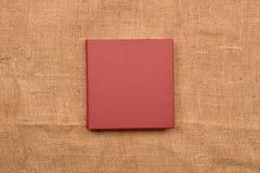 Изображение красной кожаной крышки фотоальбома на предпосылке джута Kee Стоковая Фотография