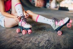 Изображение крепких и тонких ног одной девушки Она сидит на конкретных и связывая шнурках на роликах Они розовы Стоковое фото RF
