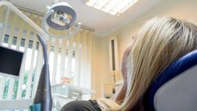 Изображение крупного плана вид сзади молодой белокурой женщины лежа в стуле дантиста стоковые изображения