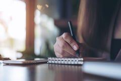 Изображение крупного плана женщины держа карандаш и писать на тетради с белым мобильным телефоном на деревянном столе Стоковое фото RF