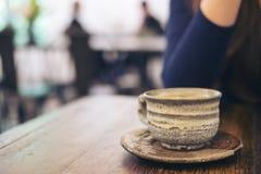 Изображение крупного плана женщины сидя в кафе с чашкой керамики горячего кофе на винтажном деревянном столе Стоковое Фото