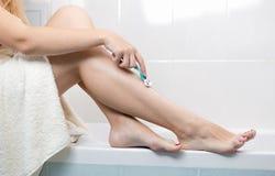Изображение крупного плана молодой женщины сидя в ванной комнате и брея ноги с лезвием бритвы Стоковое Изображение