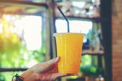 Изображение крупного плана руки ` s женщины держа стекло оранжевого холода b Стоковое фото RF