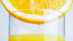 Изображение крупного плана свежего сока пропуская от оранжевой половины в прозрачном стекле Стоковая Фотография RF