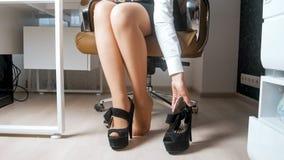 Изображение крупного плана сексуальной молодой коммерсантки принимая ботинки высоких пяток на офис Стоковое Изображение RF