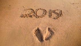 Изображение крупного плана следов ноги и 2019 номеров написанных на влажном песке на пляже моря Концепция Нового Года, рождества  стоковые изображения rf