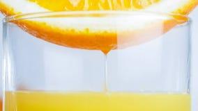 Изображение крупного плана сока пропуская от оранжевой половины в стекле Стоковая Фотография