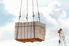 Изображение крупного плана кучи крана поднимаясь кирпичей на голубом небе Стоковая Фотография