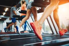 Изображение людей бежать на третбане в спортзале стоковое изображение