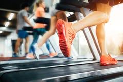Изображение людей бежать на третбане в спортзале стоковая фотография