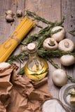Изображение макроса лапшей, грибов, яичек, бутылки масла, чеснока и розмаринового масла Сырые ингридиенты на деревянном столе Стоковые Изображения