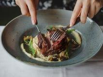 Изображение макроса вкусного блюда в голубой плите на белой предпосылке таблицы Рука режет часть сочного мяса экземпляр стоковое изображение rf