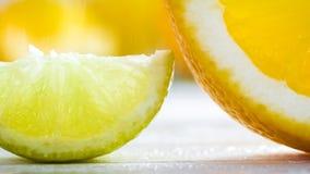 Изображение макроса влажных кусков известки и апельсина на белом деревянном столе Стоковое Изображение RF