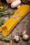 Изображение макроса желтых сырых макаронных изделий, гриба, яичек триперсток и розмаринового масла Сырые ингридиенты на деревянно Стоковые Фотографии RF