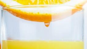 Изображение макроса капельки сока на стороне оранжевой половины падая в стекло с свежим соком Стоковое Фото