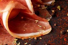 Изображение макроса отрезанной ветчины и красных специй на темной деревянной предпосылке Вкусные закуски для алкогольных напитков Стоковые Изображения