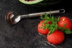 Изображение макроса продуктов арбуза с ветроуловителем металла на черной предпосылке Красные ветроуловители арбуза с листьями мят Стоковые Фото