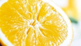 Изображение макроса сияющей влажной оранжевой половины на белой таблице Стоковое Фото