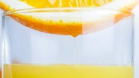 Изображение макроса сочной оранжевой половины na górze стекла с свежим соком Стоковая Фотография RF