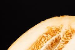 Изображение макроса сочной, сырцовой и свежей дыни Половина зрелой пульпы с семенами на черной предпосылке отрежьте дыню экземпля Стоковые Изображения