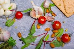 Изображение макроса томатов вишни, листьев зеленого салата, чеснока и картошек Ингридиенты для салата лета на сером цвете Стоковые Фото