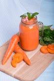 Изображение макроса smoothie моркови на голубой предпосылке ткани Здоровый напиток вытрезвителя в опарнике каменщика рядом с отре Стоковая Фотография RF