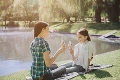 Изображение мамы и daughgter сидя на одеяле около озера Они держат мороженое в руках Девушка смотрит Стоковое фото RF