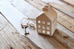 Изображение малого миниатюрного дома и старый ключ над деревенским деревянным столом Стоковая Фотография