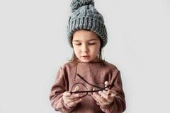 Изображение милой маленькой девочки играя в шляпе зимы теплой, нося свитере с круглыми стильными зрелищами на белой студии стоковое фото rf