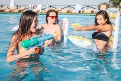Изображение моделей играя и имея потеху в бассейне Они имеют бой Стрельба молодой женщины в один другого с стоковые изображения rf