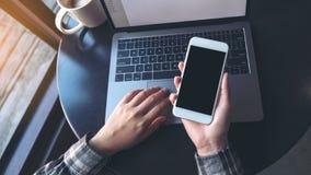 Изображение модель-макета бизнес-леди держа мобильный телефон с пустым черным экраном пока использующ компьтер-книжку на таблице стоковое фото